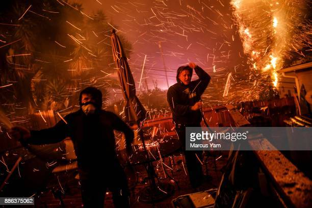 John Bain and Brandon Baker take cover from the embers as they try to help stop a fire from burning a stranger's home on December 5 2017 in Ventura...
