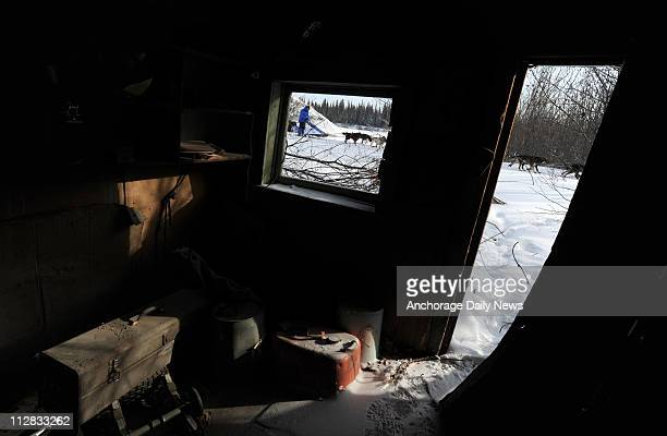 John Baker is the third musher out of the checkpoint of Nikolai in Alaska as he mushes past an old cabin on Tuesday March 9 during the 2010 Iditarod...