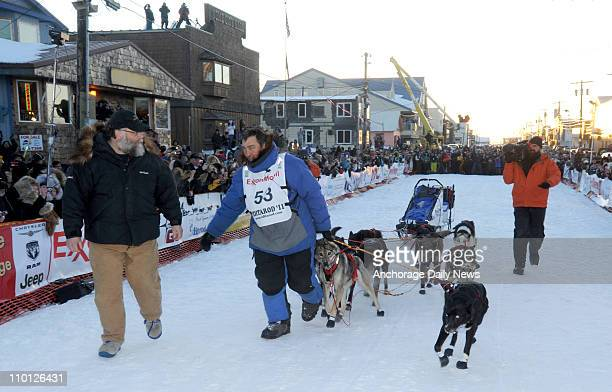 John Baker leads his team to the burled arch to win the Iditarod Trail Sled Dog Race Tuesday morning March 15 in Nome Alaska