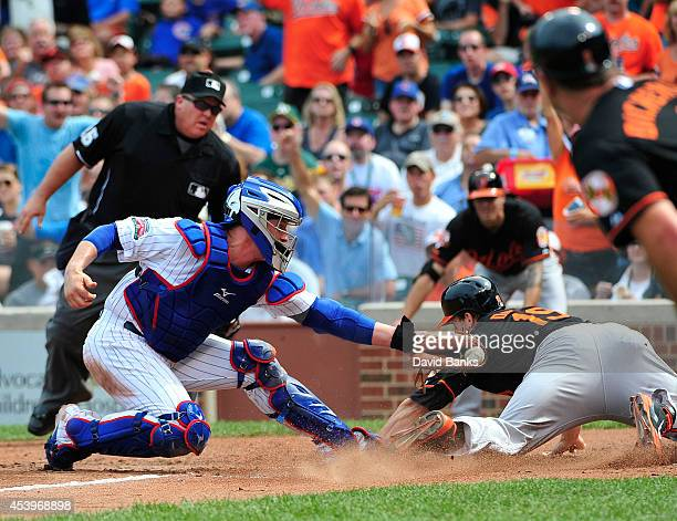 John Baker of the Chicago Cubs tags out Chris Davis of the Baltimore Orioles during the fifth inning on August 22, 2014 at Wrigley Field in Chicago,...