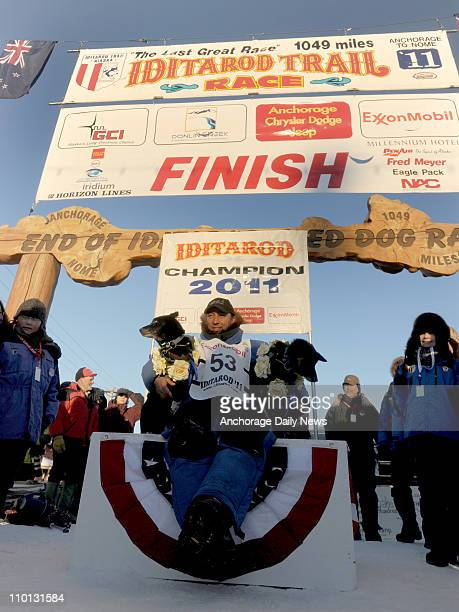 John Baker poses for a photo with his lead dogs after winning the Iditarod Trail Sled Dog Race Tuesday morning on March 15 in Nome Alaska