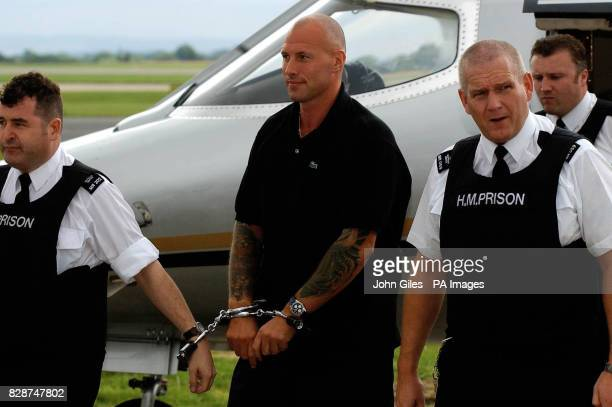 John Barber is handcuffed to prison warders as he is brought from an aircraft at Manchester Airportfollowing his extradition after being captured by...