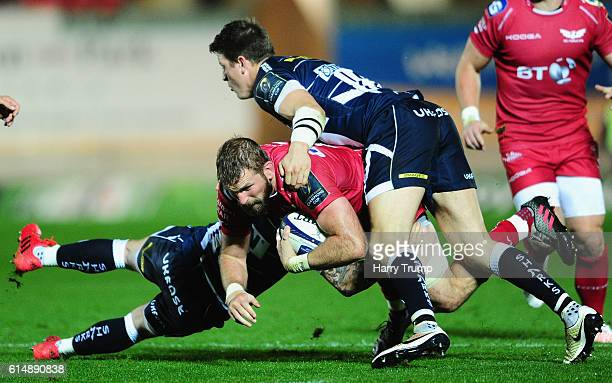 John Barclay of Scarlets is tackled by Dan Mugford of Sale Sharks and Sam James of Sale Sharks during the European Rugby Champions Cup between...