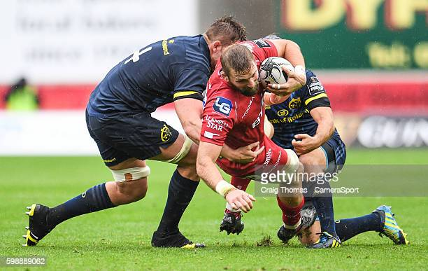 John Barclay of Scarlets is tackled by Dave Foley of Munster during the Guinness PRO12 Round 1 match between Scarlets and Munster Rugby at Parc y...