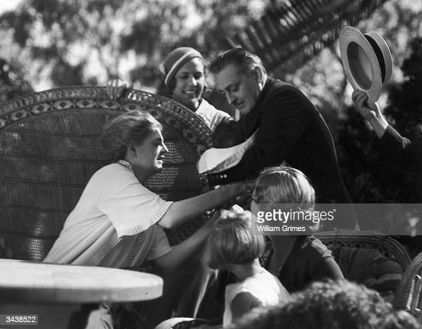 John Barrymore hands his baby son John Drew Barrymore to his sister Ethel whilst the siblings are in California to film the MGM talking picture...
