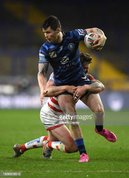 John Bateman of Wigan Warriors is tackled by Ben Hellewell of Leigh Centurions during the Betfred Super League match between Leigh Centurions and...