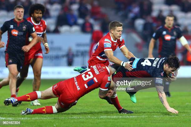 John Bateman of Wigan Warriors is tackled by Ben Kavanagh of Hull KR during the Betfred Super League at KCOM Craven Park on May 25, 2018 in Hull,...