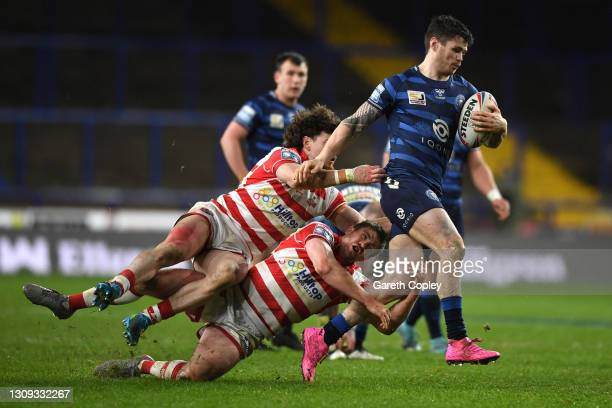 John Bateman of Wigan Warriors is tackled by Blake Wallace and Nathaniel Peteru of Leigh Centurions during the Betfred Super League match between...