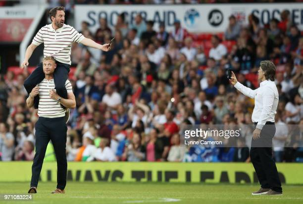 John Bishop assistant of England takes a photo of Lee Mack of England as he is carried by Andrew Flintoff of England prior to the Soccer Aid for...