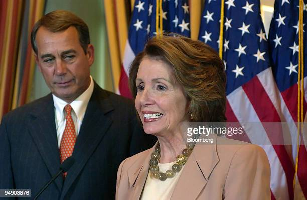 John Boehner minority leader of the US House of Representatives left listens to Nancy Pelosi speaker of the House announce the passage of an economic...