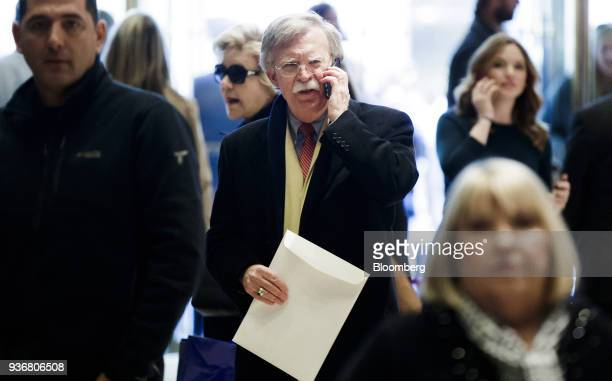 John Bolton former US ambassador to the United Nations talks on a mobile device while walking through the lobby at Trump Tower in New York US on...