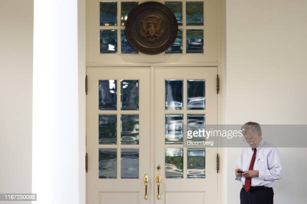 John Bolton national security adviser holds a mobile device outside the West Wing of the White House in Washington DC US on Tuesday Sept 10 2019...