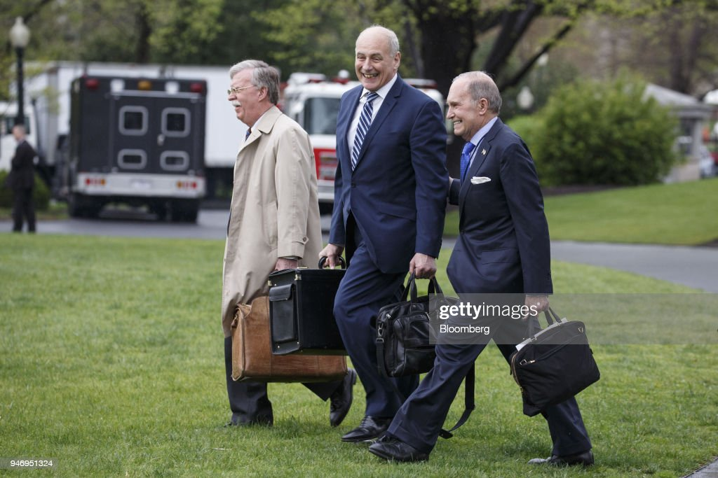 John Bolton, national security advisor, from left, John Kelly, White House chief of staff, and Larry Kudlow, director of the U.S. National Economic Council, walk towards Marine One for Miami with U.S. President Donald Trump, not pictured, on the South Lawn of the White House in Washington, D.C., U.S. on Monday, April 16, 2018. Trumpaccused China and Russia of devaluing their currencies, opening a new front in his argument that foreign governments are taking advantage of the U.S. economy to support their own expansions. Photographer: Joshua Roberts/Bloomberg via Getty Images