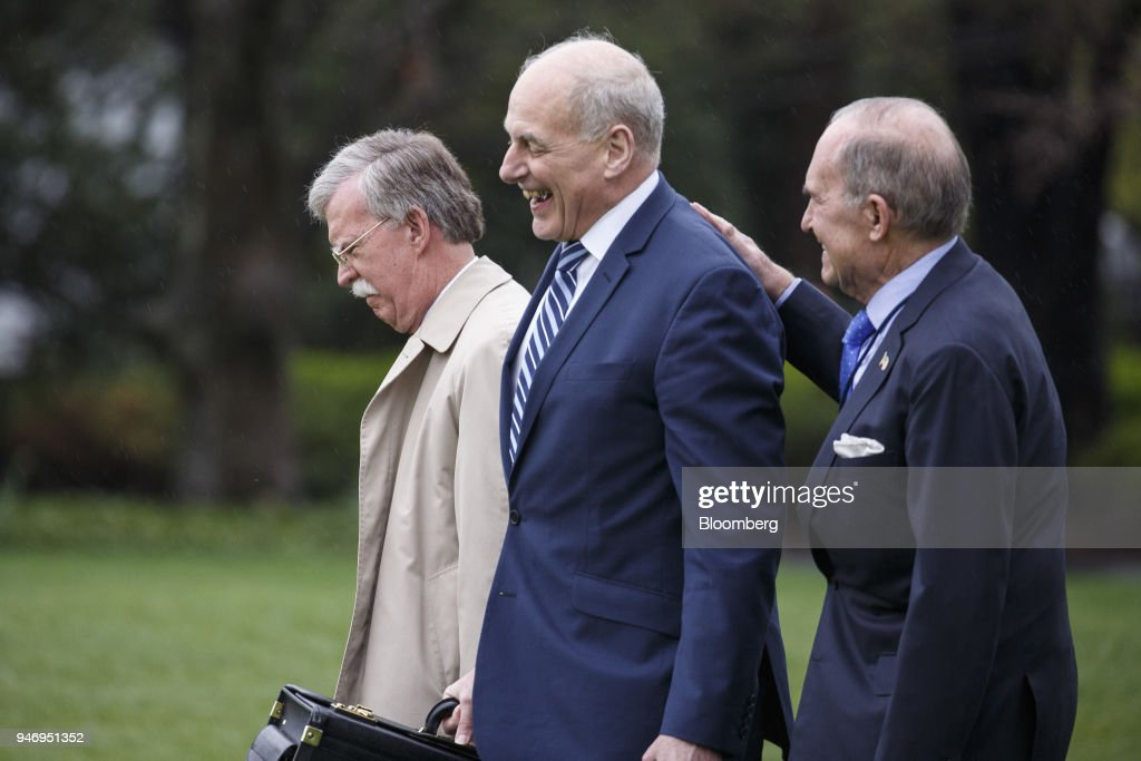 John Bolton, national security advisor, from left, John Kelly, White House chief of staff, and Larry Kudlow, director of the U.S. National Economic Council, walk towards Marine One for Miami with U.S. President Donald Trump, not pictured, on the South Lawn of the White House in Washington, D.C., U.S. on Monday, April 16, 2018. Trump accused China and Russia of devaluing their currencies, opening a new front in his argument that foreign governments are taking advantage of the U.S. economy to support their own expansions. Photographer: Joshua Roberts/Bloomberg via Getty Images