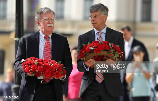 John Bolton the US National Security Advisor and William Taylor the US Ambassador to Ukraine lays flowers to a wall with portraits of Ukrainian...