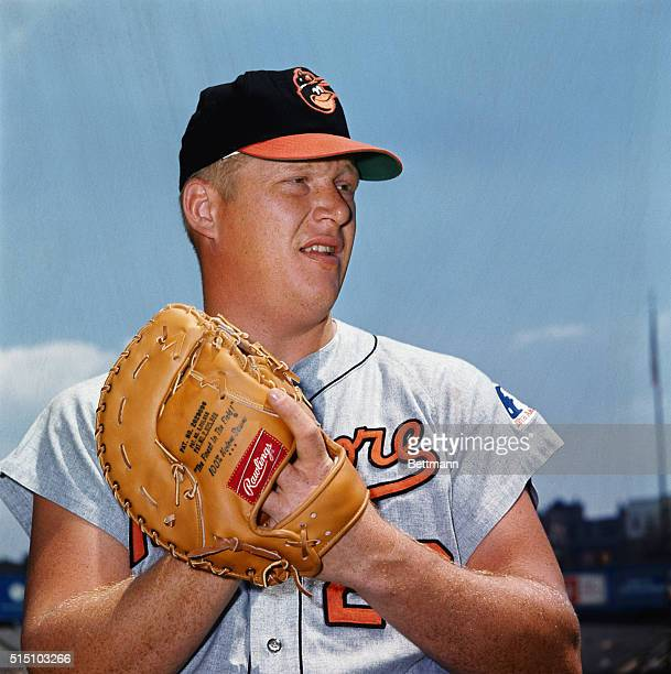 """John """"Boog"""" Powell, 1st baseman for the Baltimore Orioles, is shown in a close up shot from the waist up wearing his baseball glove."""