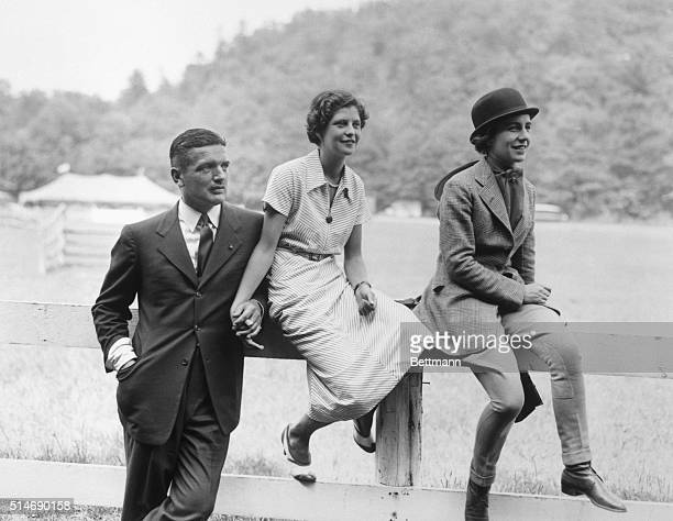 John Bouvier III father of Jacqueline Bouvier and Virginia Kernochan hold hands while Janet Lee Bouvier sits nearby The three watch the first day's...