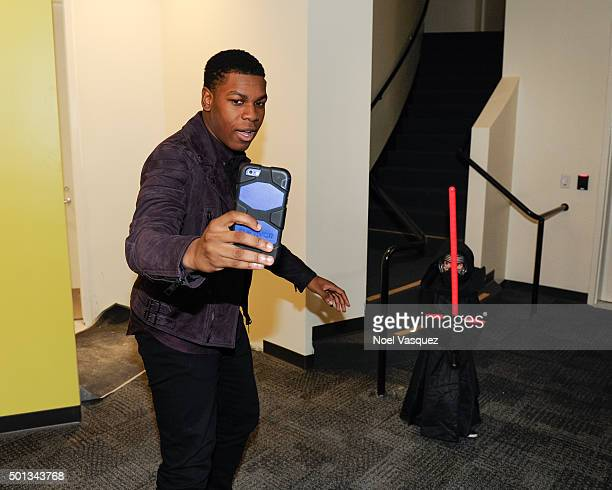 John Boyega meets a fan dressed as 'Kylo Ren' at Extra at Universal Studios Hollywood on December 14 2015 in Universal City California