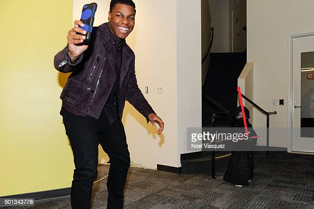"""John Boyega meets a fan dressed as 'Kylo Ren' at """"Extra"""" at Universal Studios Hollywood on December 14, 2015 in Universal City, California."""