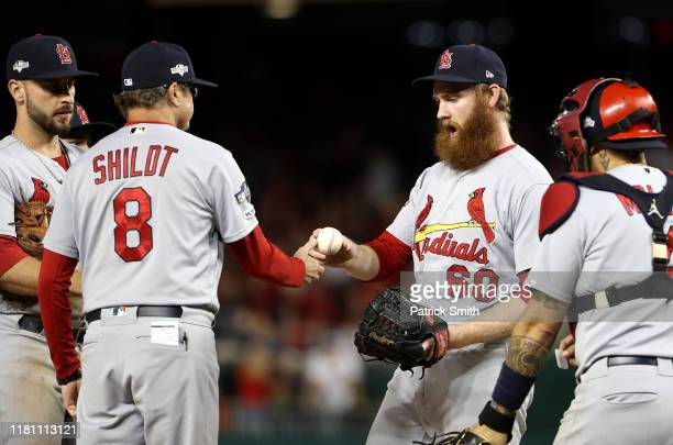 John Brebbia of the St Louis Cardinals gives the ball to manager Mike Shildt after being relieved in the sixth inning of game three of the National...