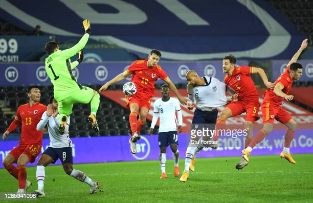 John Brooks of USA heads at goal despite the attentions of Wales goalkeeper Danny Ward, James Lawrence and Tom Lockyer during the international...