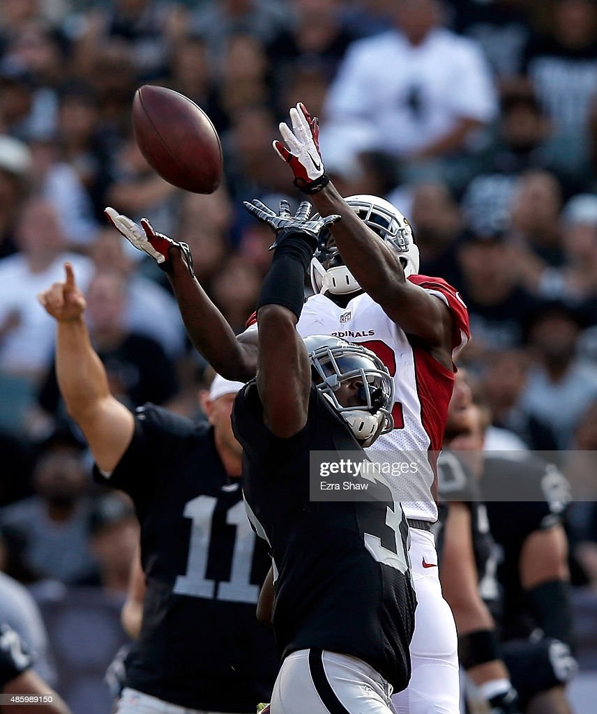 John Brown #12 of the Arizona Cardinals leaps over Neiko Thorpe #31 of the Oakland Raiders to catch the ball at O.co Coliseum on August 30, 2015 in Oakland, California.
