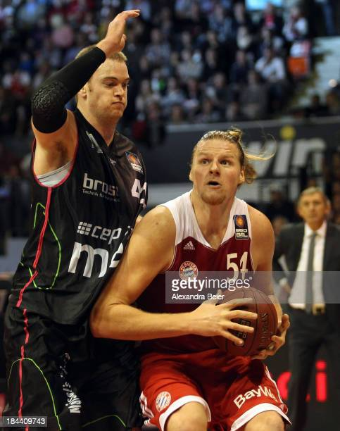 John Bryant of Bayern Muenchen is tackled by Brian Qvale of medi Bayreuth during the Basketball Bundesliga match between FC Bayern Muenchen and medi...
