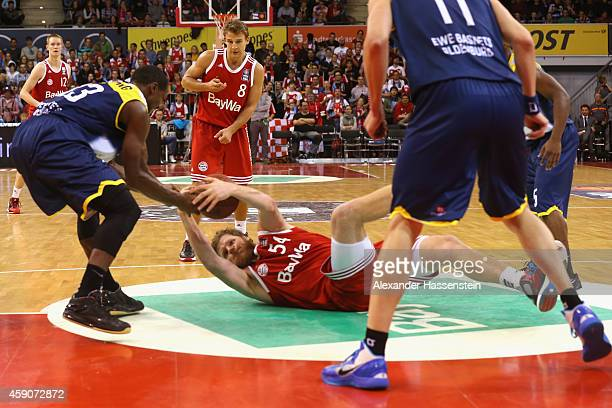 John Bryant of Muenchen battles for the ball with Rickey Paulding of Oldenburg during the Beko Basketball Bundesliga match between FC Bayern Muenchen...