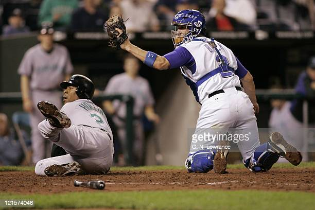 John Buck of the Kansas City Royals and Damon Hollins of the Tampa Bay Devil Rays await the umpires call after a play at the plate at Kauffman...