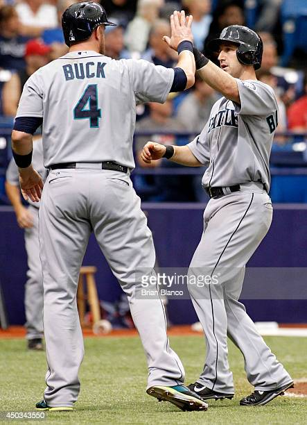 John Buck of the Seattle Mariners and Willie Bloomquist of the Seattle Mariners celebrate at the plate after both scoring off of a single by Robinson...