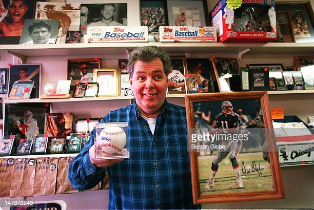 John Burke owner of The Sweet Spot a sports card shop holds up to hot items an autographed photo of Drew Bledsoe and a baseball with Mo Vaugh's...
