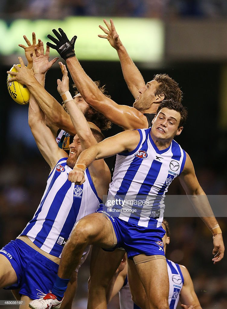 John Butcher of the Power marks the ball against Lachie Hansen (L) and Nathan Grima (R) of the Kangaroos during the round three AFL match between the North Melbourne Kangaroos and the Port Adelaide Power at Etihad Stadium on April 6, 2014 in Melbourne, Australia.