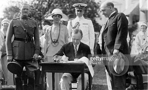 John Calvin Coolidge 30th President of the USA 19231929 signing bills on the White House Lawn General of the Armies John Joseph Pershing looks on