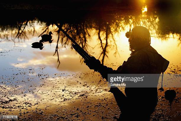 John Cameron watches for flying ducks as the sun starts to rise during a morning duck shooting at Mercer on June 16 2006 in Auckland New Zealand The...