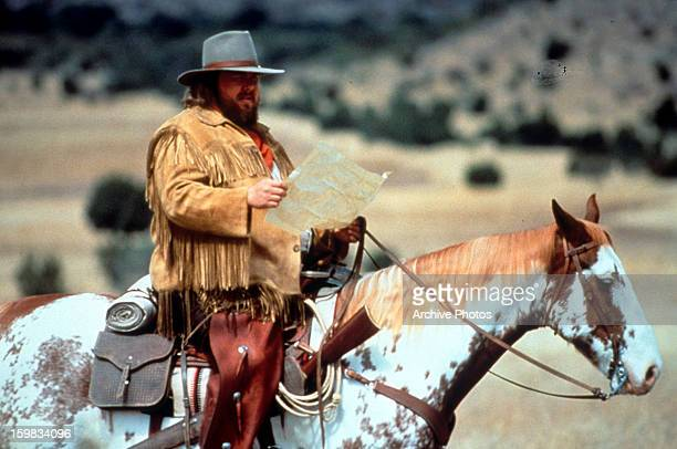 John Candy reads a map in a scene from the film 'Wagons East' 1994