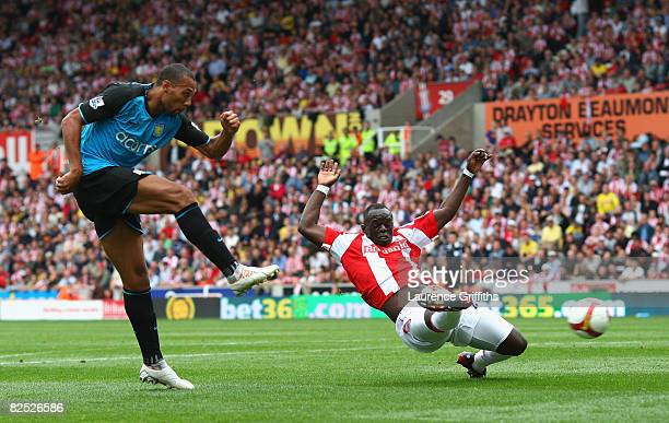 John Carew of Aston Villa scores the equalising goal past a lunging Abdoulaye Faye of Stoke during the Barclays Premier League match between Stoke...