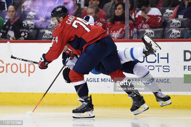 John Carlson of the Washington Capitals and Mark Scheifele of the Winnipeg Jets collide in the second period at Capital One Arena on March 10 2019 in...