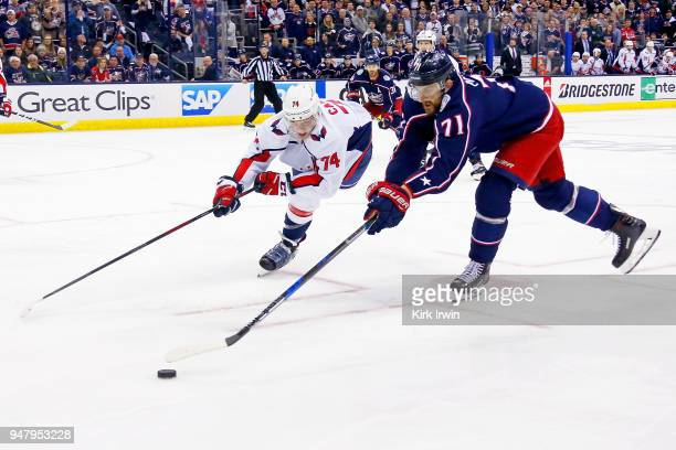 John Carlson of the Washington Capitals and Nick Foligno of the Columbus Blue Jackets battle for control of the puck during the first overtime period...