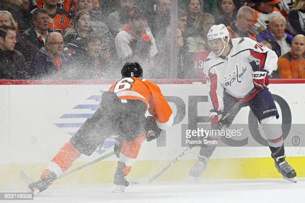 John Carlson of the Washington Capitals and Travis Sanheim of the Philadelphia Flyers battle for the puck during the first period at Wells Fargo...