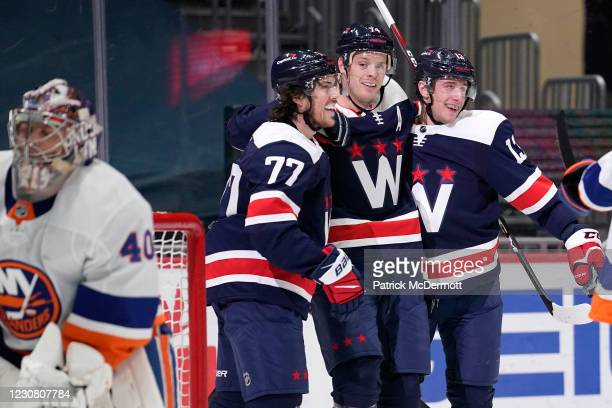John Carlson of the Washington Capitals celebrates with teammates T.J. Oshie and Jakub Vrana after scoring a goal against the New York Islanders in...