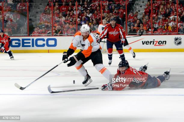 John Carlson of the Washington Capitals knocks the puck away from Sean Couturier of the Philadelphia Flyers during the first period at the Verizon...