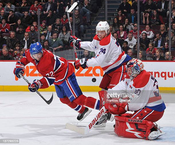 John Carlson of the Washington Capitals pushes Erik Cole of the Montreal Canadiens as goalie Michal Neuvirth stops the puck during the NHL game on...