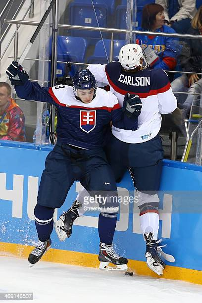John Carlson of United States is checked by Slovakia during the Men's Ice Hockey Preliminary Round Group A game on day six of the Sochi 2014 Winter...