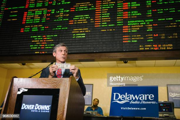 John Carney governor of Delaware holds a US ten dollar bank symbolizing the ceremonial first bet while speaking during the launch of fullscale sports...