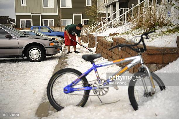John Castro shoveled hail from the front steps of a relative's home near 104th Avenue and Chambers Street Wednesday afternoon after a large, powerful...