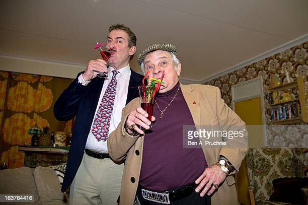 John Challis with a Del Boy lookalike pose in the 'Only Fools and Horses' themed room as they attend a photocall to launch the Ideal Home Show at...