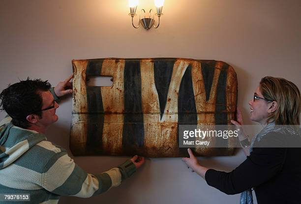 John Chalmers and Emma Smele adjust a door on their living room wall that they saved from a wrecked car that was left in a quarry and painted by the...