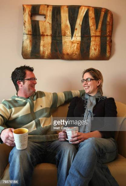 John Chalmers and Emma Smele drink tea beneath a door on their living room wall that they saved from a wrecked car that was left in a quarry and...