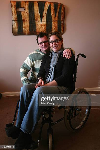 John Chalmers and Emma Smele pose for a photograph beneath a door on their living room wall that they saved from a wrecked car that was left in a...