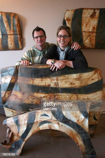 John Chalmers and Emma Smele pose for a photograph with car body sections in their living room that they salvaged from a wrecked car that was left in...
